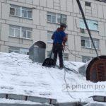 Чистка снега от снега и наледи промышленными альпинистами.